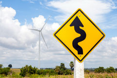 Winding road sign and windmill background in wind farm. Royalty Free Stock Images