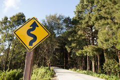 Winding road sign. Yellow winding road ahead sign in pine wood mountain street royalty free stock photo