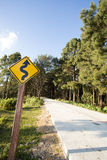 Winding road sign. Yellow winding road ahead sign in pine wood mountain street stock images