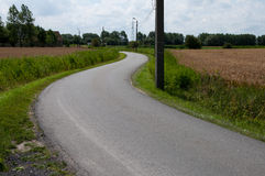 Winding road. A small curved road between field of wheat Stock Photo