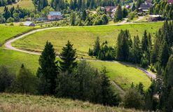 Winding road to village through grassy hillside. Winding road to village through grassy hille with spruce forest. lovely early autumn countrye landscape Royalty Free Stock Photo
