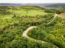 Winding road trough the forest on a hill top. Aerial shot using a drone over the mountains Stock Photography