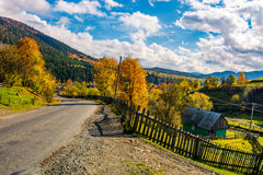 Winding road through village in mountains. Beautiful Carpathian rural scenery. gorgeous afternoon autumn weather with stunning sky Stock Photos