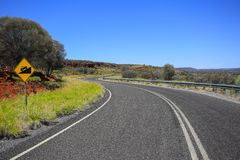 Winding road. Yellow road sign. Attention twisting road stock image