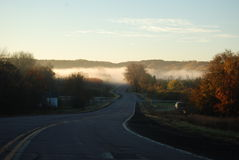 Winding rural road approaching fog-filled river valley Stock Photography