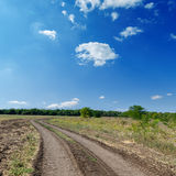 Winding rural road under cloudy sky Royalty Free Stock Images
