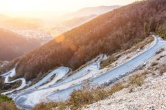Winding serpentine road among rising to the rocky mountains. During sunset lights.  stock image