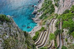 Winding stairs leading down to sea on a steep slope royalty free stock photo