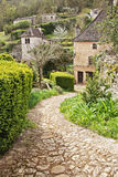 Winding Stone Path to Stone Cottage. Stone path winding down to stone cottage in lush green spring foliage Stock Image