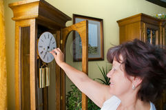 Winding up. Woman winding up the upstanding clock royalty free stock image