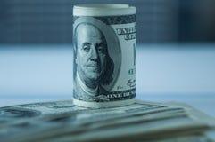 Winding van de benamingen van honderd Amerikaanse dollars op een onscherpe achtergrond royalty-vrije stock afbeeldingen