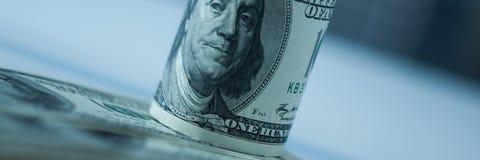 Winding van de benamingen van honderd Amerikaanse dollars op een onscherpe achtergrond Op de dollars op worden verspreid die stock afbeeldingen