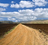 Winding white dirt road. And cloudscape Royalty Free Stock Image