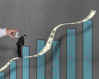 Winding winder on businessman's back standing on growing money t. Businessman standing on growing money trend with winder on his back, another man's hand winding Stock Photo