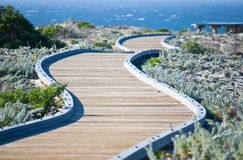 Winding wooden walkway leading towards the ocean Stock Images