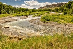 Meandering Wyoming Stream. Winding Wyoming stream in Wyoming with trees and butte in the background with blue sky and white clouds stock images