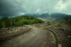 Windirglandweg langs de hellingen die van Etna Mount tot de boomlijn onder stormachtige hemel leiden stock foto
