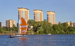 Windjammer on river. Windjammer with white-orange sail on river Stock Image