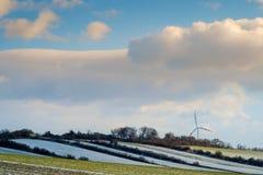 Windkraftanlage in der Landschaft mit Wolken und mit einem wenigen Schnee Stockfotos