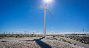 Windkraftanlage gegen Sonnen- und Windmühlenbauernhof Lizenzfreie Stockbilder