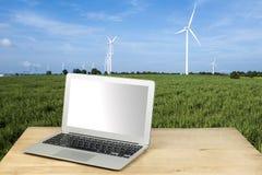 Windkraftanlage mit Laptop auf Holztisch Weltweites Energie busin Lizenzfreies Stockfoto