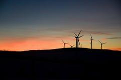 Windkraftanlagebauernhof bei Sonnenuntergang Stockfotografie