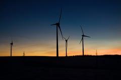 Windkraftanlagebauernhof bei Sonnenuntergang Stockfotos