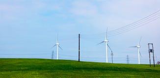 Windkraftanlagen auf einem grünen Hügel Lizenzfreie Stockfotografie