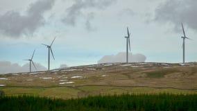 Windkraftanlagen auf einem Hügel mit Flecken des Schnees Stockfotografie