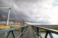 Windkraftanlagen auf niederländischem Ackerland im Sonnenschein Lizenzfreies Stockbild