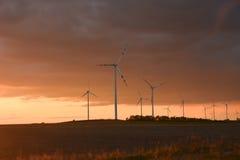 Windkraftanlagen bei einem Sonnenuntergang Stockfotografie