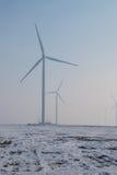 Windkraftanlagen bewirtschaften auf Feld mit Nebel und Schnee lizenzfreie stockbilder