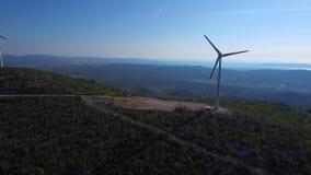Windkraftanlagen an der Spitze des Berges durch das Meer an einem sonnigen Tag stock video