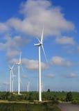 Windkraftanlagen, die Strom mit blauem Himmel erzeugen Stockfotografie