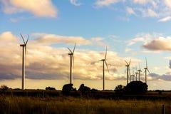 Windkraftanlagen in einer Windkraftanlage bei Sonnenuntergang stockbilder