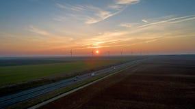 Windkraftanlagen entlang der Landstraße bei Sonnenuntergang, Frankreich lizenzfreie stockbilder