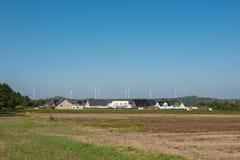 Windkraftanlagen hinter einer Neubauregelung in der ländlichen Einfassung Lizenzfreies Stockbild