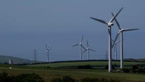 Windkraftanlagen 4K in den Sommertagesstromleitungen des blauen Himmels für Strom im Hintergrund Großbritannien stock footage