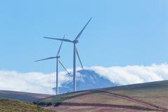 Windkraftanlagen mit Bergen und Wolken im Hintergrund Lizenzfreie Stockfotografie