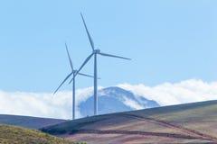 Windkraftanlagen mit Bergen und Wolken im Hintergrund Lizenzfreie Stockfotos