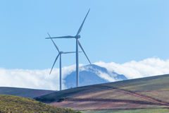 Windkraftanlagen mit Bergen und Wolken im Hintergrund Lizenzfreies Stockbild
