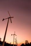 Windkraftanlagen mit Stromleitung auf dem Sonnenuntergang Stockfotografie