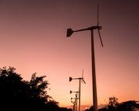 Windkraftanlagen mit Stromleitung auf dem Sonnenuntergang Stockbilder