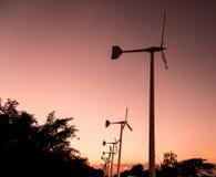 Windkraftanlagen mit Stromleitung auf dem Sonnenuntergang Lizenzfreies Stockbild