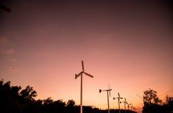 Windkraftanlagen mit Stromleitung auf dem Sonnenuntergang Stockbild