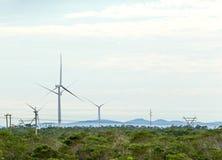 Windkraftanlagen mit Wolken im Hintergrund und Bäumen im Vordergrund Stockbild