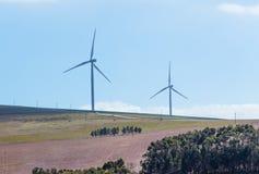 Windkraftanlagen mit Wolken im Hintergrund und Bäumen im Vordergrund Stockfotos