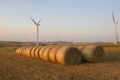 Windkraftanlagen und Ballen Heu auf einem Gebiet Stockbilder