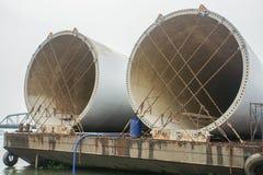 Windkraftanlageturm gesichert mit Ketten auf Lastkahn für Transport per Schiff lizenzfreies stockfoto
