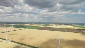 Windlandbouwbedrijven op plattelandsgebieden tegen de achtergrond van landbouwgebieden onder een blauwe hemel Luchtonderzoek stock videobeelden